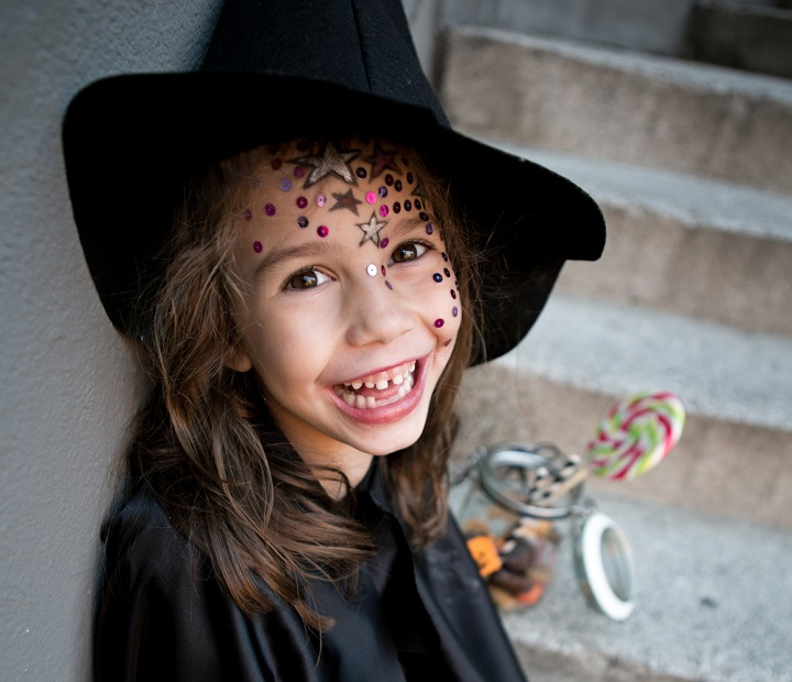Girl in a Witch Costume With Halloween Treats
